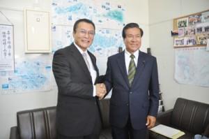 勇退の記者会見で、後継に指名した向井俊夫氏(左)と握手を交わす与力雄氏=5日、大島支庁記者クラブ