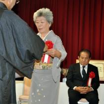 表彰を受ける中村スエさん(中央)と鹿児島沖洲会の原田孝造会長(右)=1日、和泊町のホテル