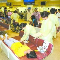 ロビーで傷病者治療を訓練する職員ら=25日、奄美市