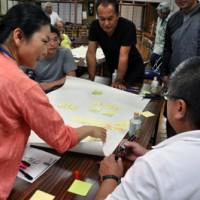 ワークショップでグループごとに意見をまとめる参加者=23日、和泊町の国頭字公民