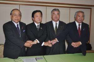 県議選への立候補会見で支援の市議と握手を交わす伊東隆吉氏(左から2人目)=4日、奄美市名瀬のホテル