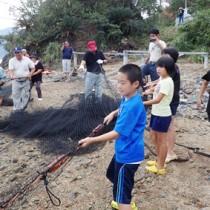 見張り台の合図を受け、網を引き上げる小中学生のモニター体験者たち=18日、宇検村芦検
