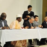 協定書に署名するギニア共和国のセンクン・シラ特命全権大使(左)と徳之島3町長=19日、伊仙町