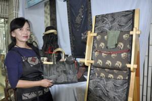 大島紬と西陣織を組み合わせた作品を手に応募を呼び掛ける貴島さん=奄美市名瀬の紬会館