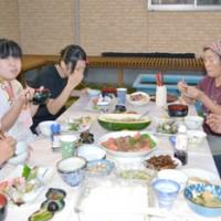 宿泊先の民家で夕食を囲み、楽しそうに会話する修学旅行生(左)=20日、与論町