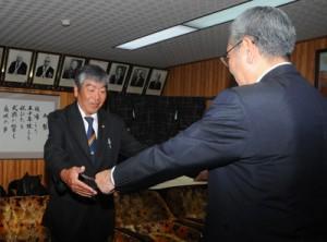 朝山毅市長から表彰状を受け取る大川さん(左)=22日、奄美市役所
