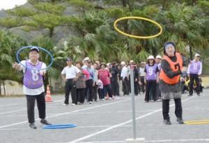 ポール目掛けてフープを投げる選手たち=9日、龍郷町補助グラウンド