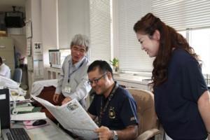 原選手ドラフト指名を報ずる本紙記事を笑顔で読む喜界町の役場職員=24日午後