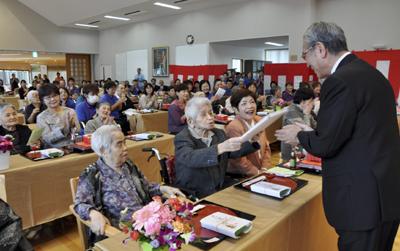 祝賀会で朝山市長から記念品を受け取る入所者=2日、奄美市住用町の住用の園