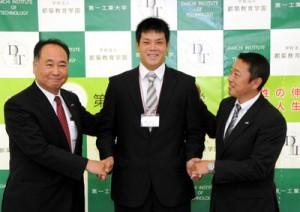 原選手(中央)と握手を交わすスカウトの鳥原さん(左)と松田さん=4日、第一工大