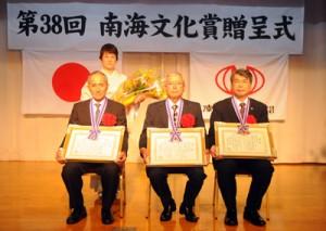 南海文化賞を贈られた中山氏、保会長、屋村校長(前列左から)。後列は中山氏の妻・美智代さん=4日、奄美市名瀬のあまかん
