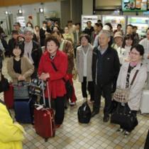 奄美大島に到着し歓迎を受ける広島発のツアー客ら=21日、奄美空港