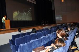 ウミガメの産卵現場を写真で紹介しながら食害の実態を報告する興さん=29日、奄美市名瀬