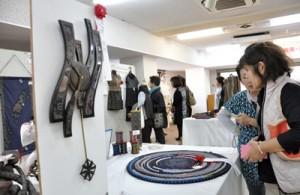 京都府知事賞に輝いた壁時計など入賞作品に見入る来場者=14日、奄美市名瀬の紬会館