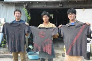 出来上がった泥染めのTシャツを手にする柿田投手、関根外野手、砂田投手(左から)=12日、龍郷町戸口