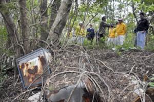 パトロールで山林に捨てられた冷蔵庫を確認する参加者=12日、奄美市名瀬