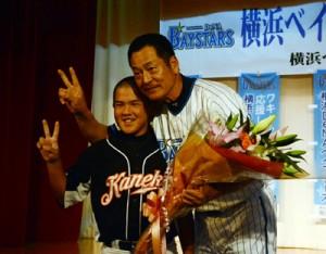 駒沢大奄美OBからの花束を受け取り、笑顔で記念撮影する中畑監督=10日、奄美市名瀬