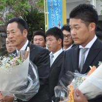 歓迎の花束を受け取る中畑清監督(左)と筒香嘉智選手=5日、奄美空港