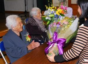 忘年会で花束を受け取る本山イ子さんと松田ミチ子さん(左から)=30日、龍郷町秋名