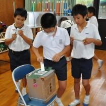 模擬投票で意中の候補に1票を投じた児童ら=21日、徳之島町の神之嶺小学校