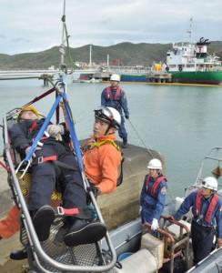 タンカー(奥)からの油流出を想定、海中からの負傷者救出などを行った訓練=25日、龍郷町