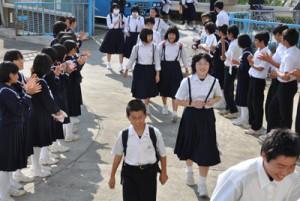 口之津中生徒を拍手で出迎える与論中生徒=19日、与論中学校