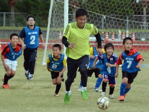 親子で対戦するミニゲームに参加する元日本代表の小倉さん=29日、太陽が丘総合運動公園陸上競技場