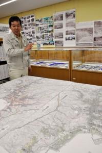 名瀬の歩みを振り返る写真と地図について説明する岩多さん=9日、奄美図書館
