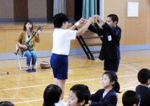 別府さんの島唄に合わせて手遊びする児童たち=19日、節田小学校