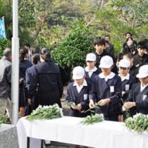 復帰運動の指導者・泉芳朗の胸像へ献花する児童生徒ら=25日、奄美市名瀬の「おがみ山公園」