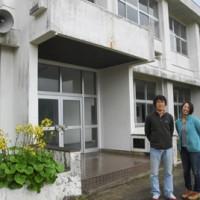 県内初のサンゴ礁研究施設が開設される旧早町小校舎。手前は渡辺講師、山崎研究員(左から)=17日、喜界町