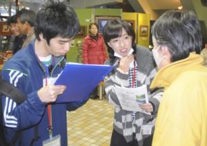 「奄美観光強化」をテーマに空港利用客を対象にアンケート調査を行う奄美情報処理専門学校の学生たち=17日、奄美空港