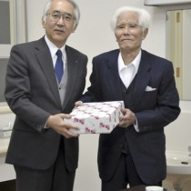 「ふるさとお楽しみ便」を受け取る入所者代表の山田さん(右)=16日、奄美市名瀬の奄美和光園