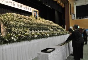 献花して樺山資敏元町長の冥福を祈る参列者ら=7日、伊仙町