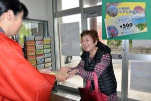 販売初日に商品券を買い求める女性=1日、龍郷町商工会。右枠は龍郷町のプレミアム商品券