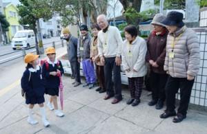 笑顔で登校児童とあいさつを交わすメンバーたち=24日、奄美市