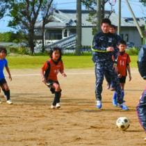 プロ選手から基本の動きを学んだサッカー教室=21日、与論町総合グラウンド
