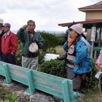 ガイド(中央)の案内で与論城跡を回る加計呂麻島民泊協議会会員=18日、与論島