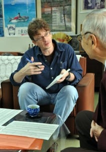 大島紬の歴史について取材するファクラーさん(奥)=21日、奄美市名瀬の大島紬会館