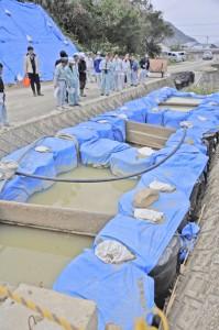 嘉渡第2小川地区の沈砂地を視察する赤土等流出防止合同パトロール参加者ら=20日、龍郷町