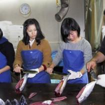 真剣な表情で魚さばき体験に取り組む須磨友が丘高校の生徒ら=22日、奄美市名瀬