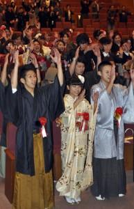 万歳を三唱して晴れの門出を祝う新成人=3日、龍郷町りゅうゆう館