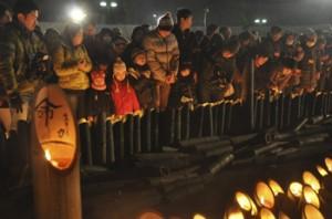 震災の犠牲者を悼み、竹灯篭のろうそくをともす人たち=17日午前5時46分、神戸市中央区