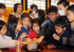 南極の氷を興味津々な様子で触る子どもたち=7日、大和村体育館