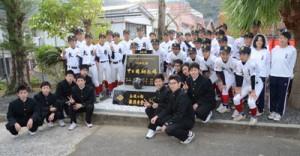 甲子園初出場を記念して建立された記念碑と野球部員ら=24日、奄美市