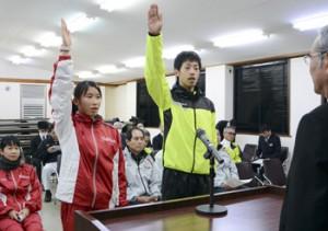 力強く選手宣誓する山下良祐、濵崎優汐の両選手(右から)=20日、奄美会館