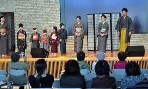 観光客を前に大島紬を披露するモデルたち=24日、奄美市笠利町の県奄美パーク