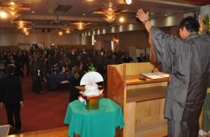 新年の飛躍に期待を込めて万歳三唱する出席者=元日、奄美市名瀬の集宴会施設