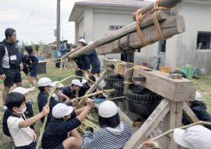 さたぐるまを使ってサトウキビを搾る子どもたち=28日、和泊町の国頭小