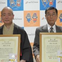 第11回あましん地域貢献賞を受賞した越間氏(左)と有馬氏=13日、奄美市名瀬のホテル